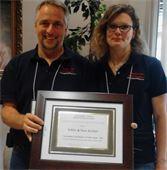 Eddie Archer and Tara Archer receiving an award