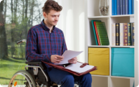 Man in a wheelchair is holding documents