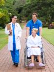caregivers assisting an elderly