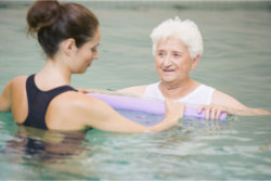 Swimming instructor assisting old woman to swim