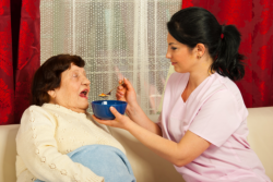 caregiver feeding senior patient