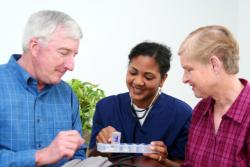 caregiver giving medicine to senior patient