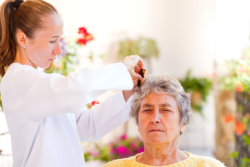 Caregiver is combing the hair of the old lady
